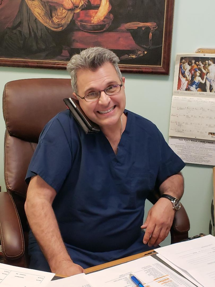 Dr. John Cozzarelli on the phone at his desk smiling